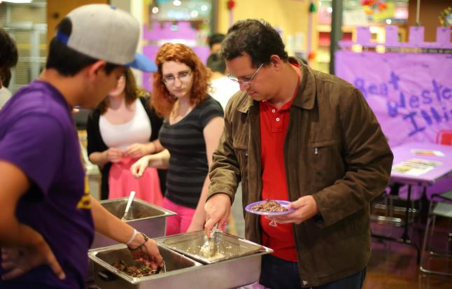Image of international student serving food samples to members of the UNI community